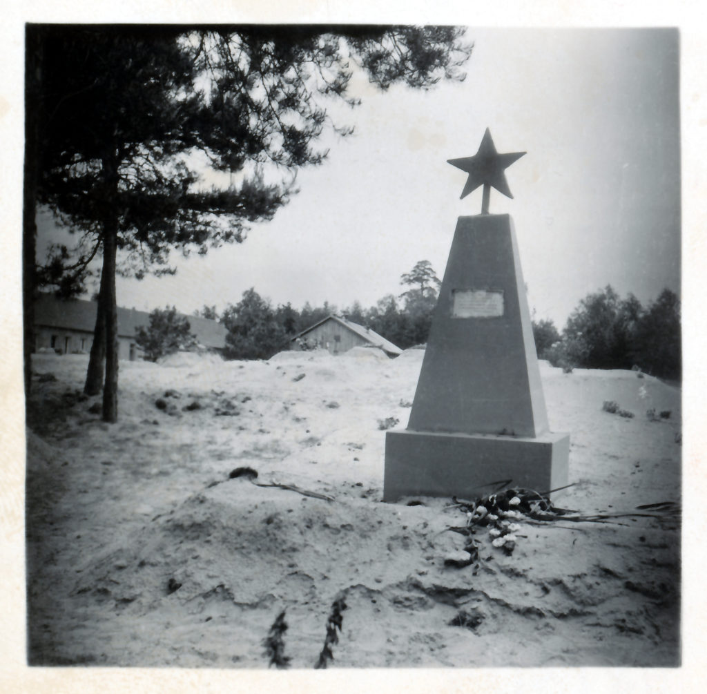 Ein sowjetisches Denkmal und Gräber, links im Hintergrund die Ostseite der ehemaligen SS-Bauleitung Ravensbrück, Sommer 1945. Fotograf/in unbekannt (MGR/SBG, Foto-Nr. 98/301)