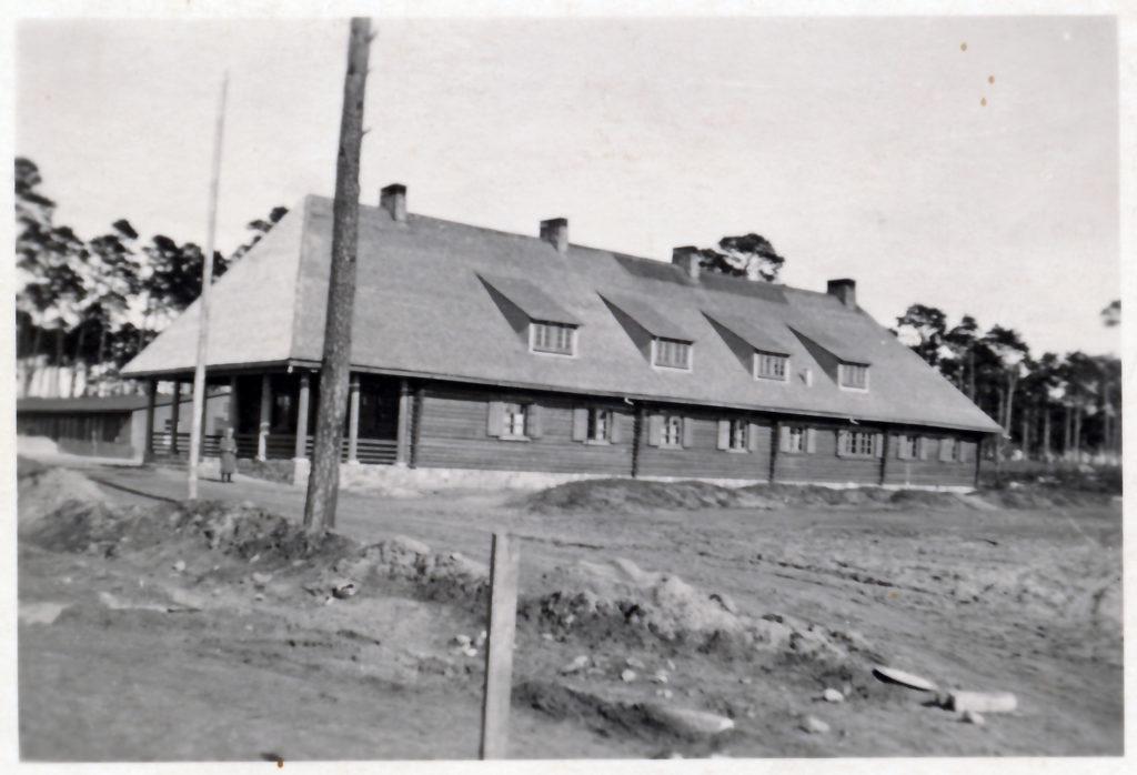 Der Eingang zum WVHA-Ausweichlager, vorne das Holzblockhaus und im Hintergrund Baracken des Ausweichlagers, April 1944. Fotograf/in unbekannt (MGR/SBG, Foto-Nr. 99/130)